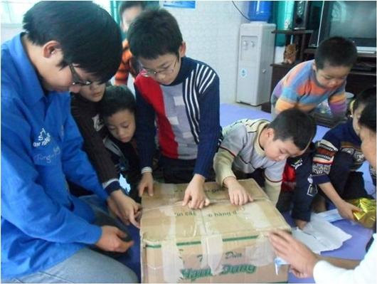 Bạn Tùng - sv K22 - Đội phó Đội SVTN đang tặng quà và giúp các em có hoàn cảnh đặc biệt tại trung tâm bóc quà